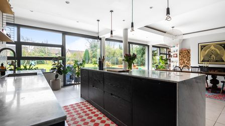Photograph showing the inside of a contemporary modern kitchen with floor to ceiling windows and a black wooden breakfast bar