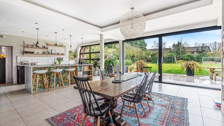 Photograph showing a contemporary kitchen dining room with lots of light flooding in and views over the gardens