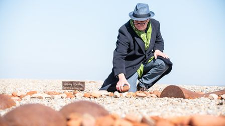 Ian Griffiths placing a stone around 'The Angel of the East' on Aldeburgh beach. Picture: Sarah