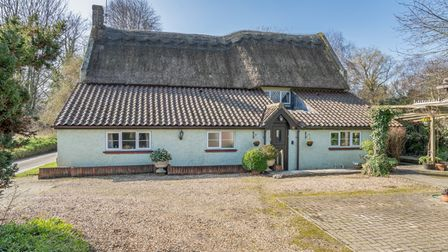 Photograph showing a pretty period cottage with thatched roof and large shingle driveway in front