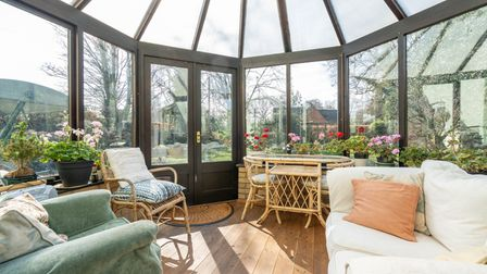 Photograph showing the inside of a domed conservatory overlooking a cottage-style garden