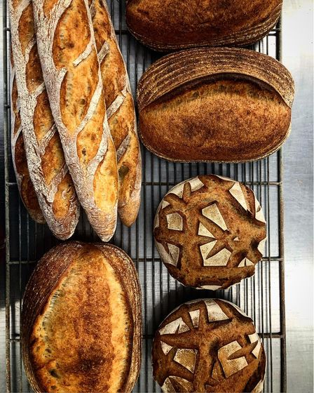 Loaves of sourdough bread and baguettes on a cooling rack from Filo and Twine