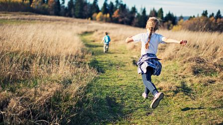 Little hiker girl and her brother hiking on path between fields. The girl is jumping. Sunny autumn d
