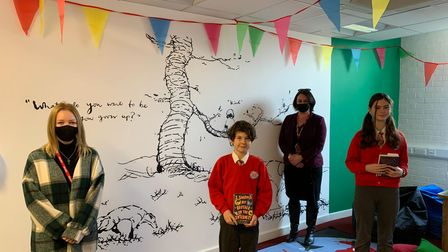 Emily, Noah Gearing, Roxy Down and Hannah showing off the prominent art work in the new reading area