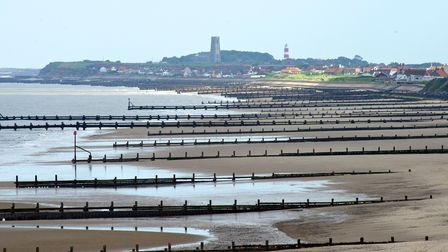 Mundesley beach in the early summer sun with Bacton, Walcott and Happisburgh lighthouse in the backg