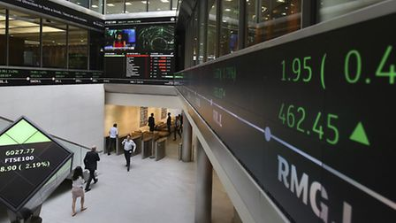 A city worker looks at a stock ticker screen at the London Stock Exchange in the City of London. PRE