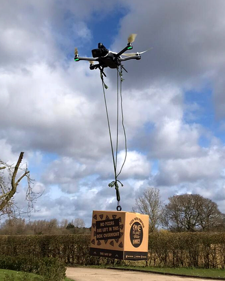 An image of a drone transporting a box of pizza.