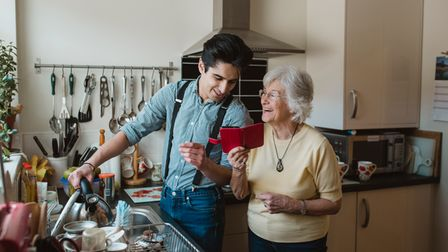 Senior woman is showing something to her grandson on her smart phone while he fills the kettle at th