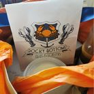 Rocky Bottoms crab logo with orange paper in a cardboard box