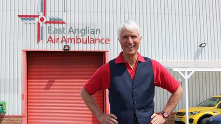 Patrick Peal smiles in front of East Anglian Air Ambulance warehouse