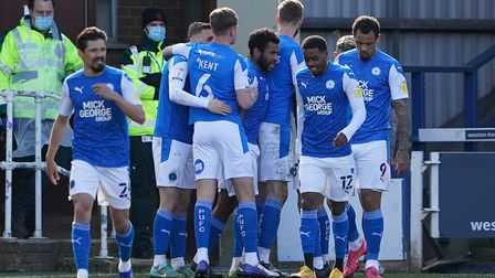 Peterborough United players celebrate their first goal scored by Siriki Dembele (hidden) during the