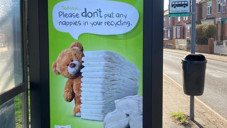 A bus stop with Suffolk Waste Partnership's poster urging people not to put nappies in recycling bins