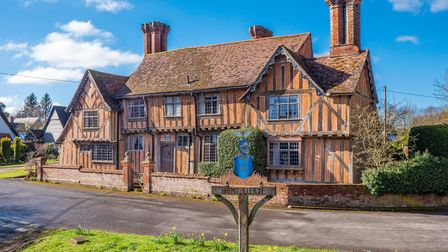 Photograph showing a large timber framed Tudor property with impressive chimneys overlooking village green