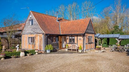 Photograph showing a timber framed brick-built self contained annexe with shingle driveway