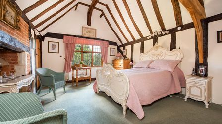 Photograph showing inside a large double bedroom with vaulted timber ceiling, carpeted floor and ornate white bed