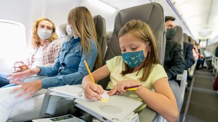Portrait of a happy girl traveling and coloring in the plane while wearing a facemask – travel