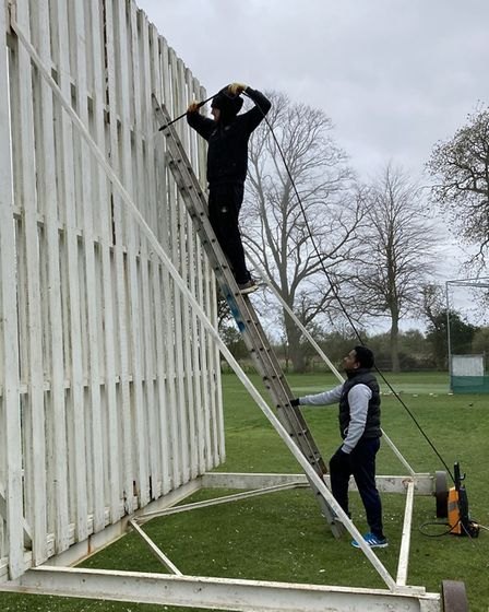 Joe Clark up the ladder against the sight screens with Udana Ranatheenga standing at the bottom