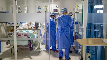 Health workers wearing full personal protective equipment (PPE) tend to a patient on the intensive c