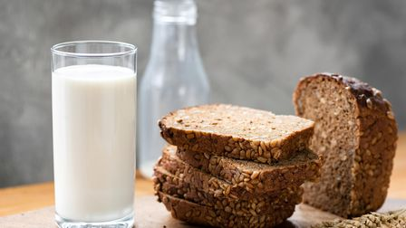 Rye bread with sunflower seeds and glass of milk on rustic wooden table