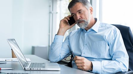 Executive senior businessman using his mobile phone and talking wih somebody while working laptop in