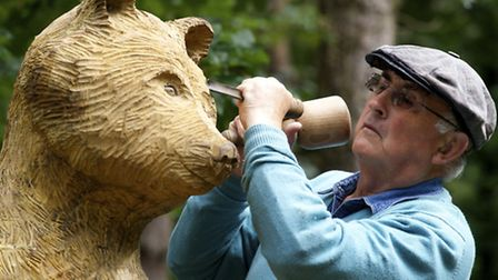 Mike Thody with his wooden sculpture of a bear. Picture: MARK BULLIMORE