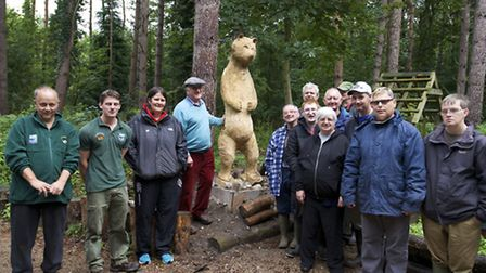 Mike Thody (centre left) unveils his wooden sculpture of a bear called Ursula at North Norfolk Distr