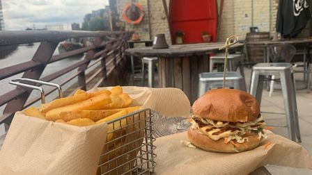 A burger and chips on a table on The Boathouse Cafe and Bar riverside terrace
