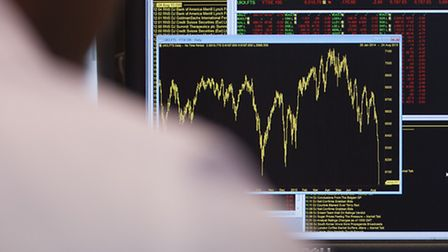 An office worker views a graph showing movement in the FTSE 100 Index, as it fell by as much as 190