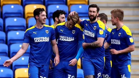 AFC Wimbledon's Joe Pigott (centre) celebrates scoring their side's first goal of the game during th