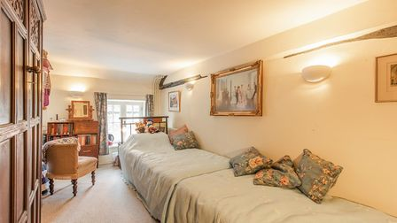 Photograph showing a long narrow bedroom with a sash window on the far wall and two single beds pushed together