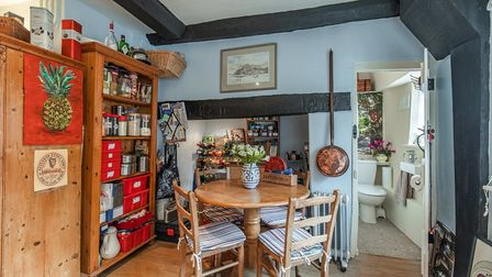 Photograph showing the corner of a country-style kitchen with small table and chairs and pantry-style cabinet