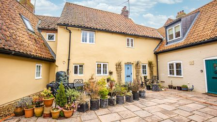 Photograph showing the outside of a pretty yellow cottage with patio courtyard out front with pots and planters