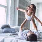 Dad and daughter playing on double bed in London shared apartment
