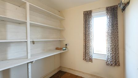 Photograph showing the corner of a room with lots of built in storage space and a window dressed in floral curtains