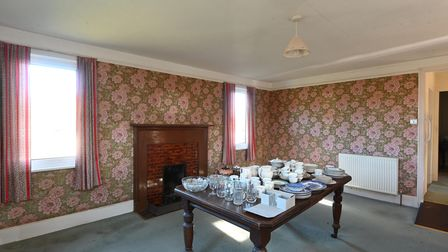 Photograph showing a dated living room with patterned floral wallpaper and large partly tiled feature fireplace
