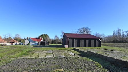 Photograph showing a bungalow and substantial outbuilding in a rural field under blue skies