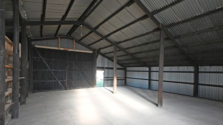 Photograph showing inside a substantial barn with vaulted ceiling and supporting columns