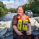 Mum holding daughter on her lap on a boat