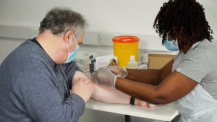 A nurse takes a blood sample from a man
