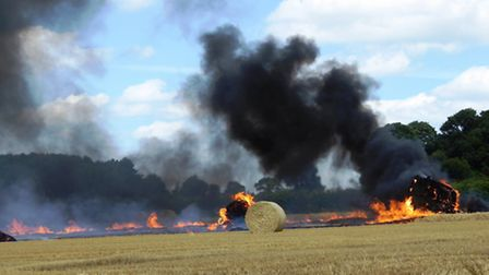 Flames and smoke spread across a stubble field after a baler fire at Edgefield, near Holt. Picture: