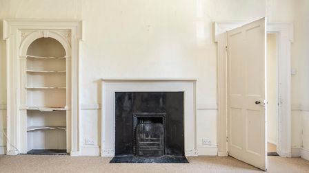 Photograph showing a sitting room with cast iron fireplace in the centre, alcove book shelves to the left and high ceilings