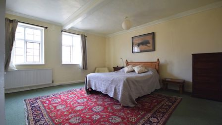 Photograph of large double bedroom with bed in the centre and high white ceilings with pale yellow painted walls