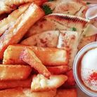 Pita bread topped with slices of halloumi, fries, salad and yoghurt dip