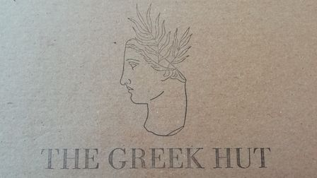 A cardboard box with a sketch of a traditional Greek bust on and the words The Greek Hut