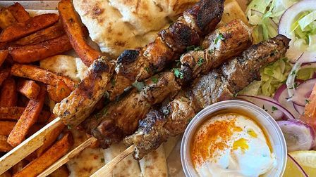 Three skewers of meat and a pot of dip on top of pita bread, with fries and salad
