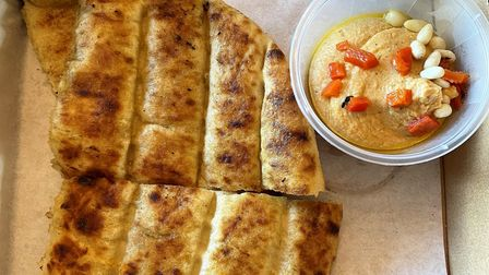 Two slices of pita bread with a pot of red pepper hummus topped with red pepper and pine nuts