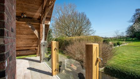 Photograph showing a glass fronted balcony attached to a timber extension overlooking green lawns under blue sky