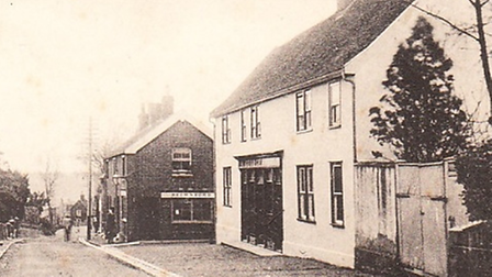A sepia photo of The George pub in Wickham Market, a white building with a tree next to it