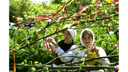 Tying ribbons on the May Tree at a Kentwell Hall Tudor weekend event in 2003
