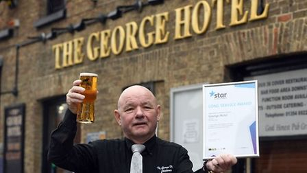 Licensee of George Hotel in Chatteris Robbie Lyons has scooped a long service award to mark his 20th anniversary at the helm